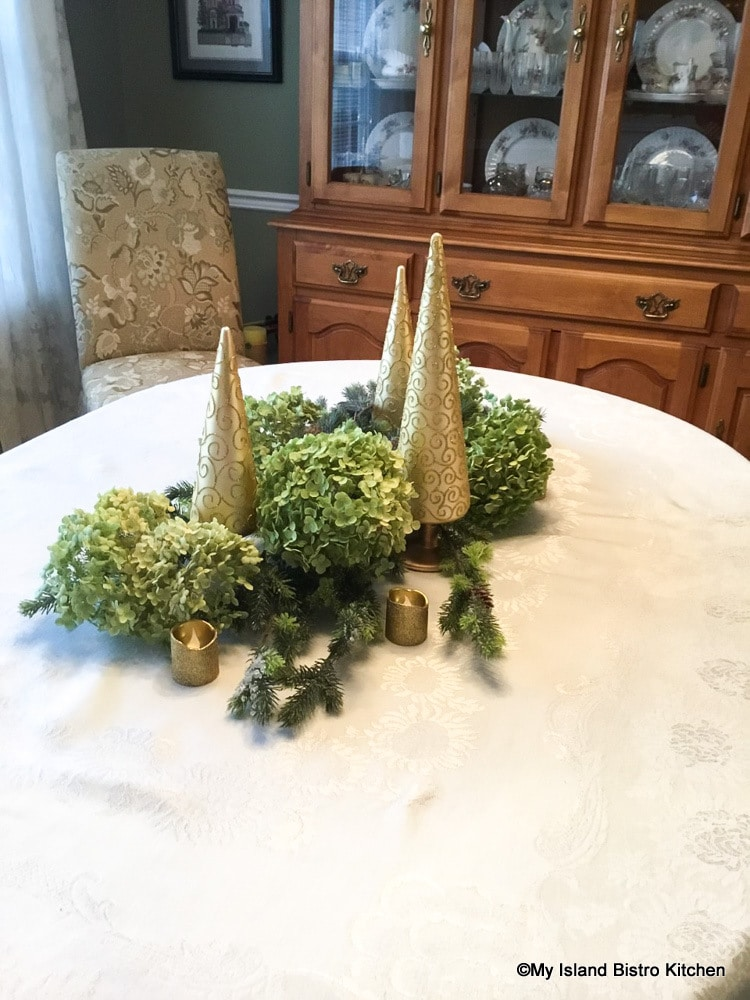 Creating a holiday tablescape with faux greenery, dried hydrangea, and gold-colored trees