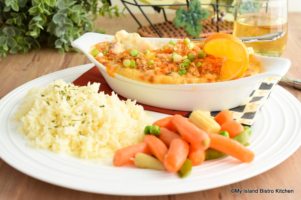 Au gratin dish filled with baked haddock in cream sauce served with basmati rice and a medley of stir-fried vegetables