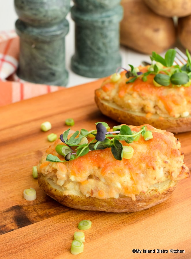 Melted cheddar cheese and bright colored pea shoots top twice-baked potatoes