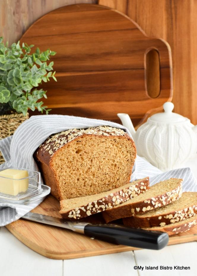 Loaf of Porridge Bread nestled inside a tea towel