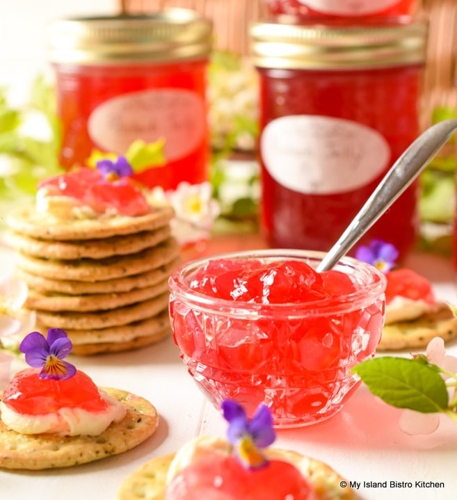 Pretty red jelly in glass bowl with jars of the jelly in the background