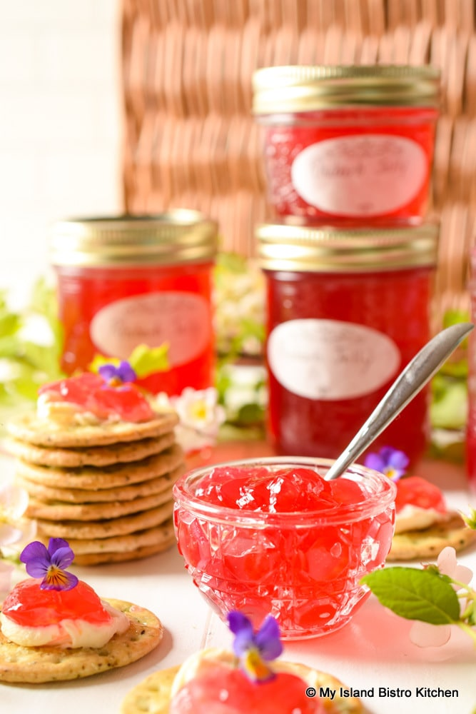 Stack of jars filled with red jelly alongside a dish of jelly and crackers