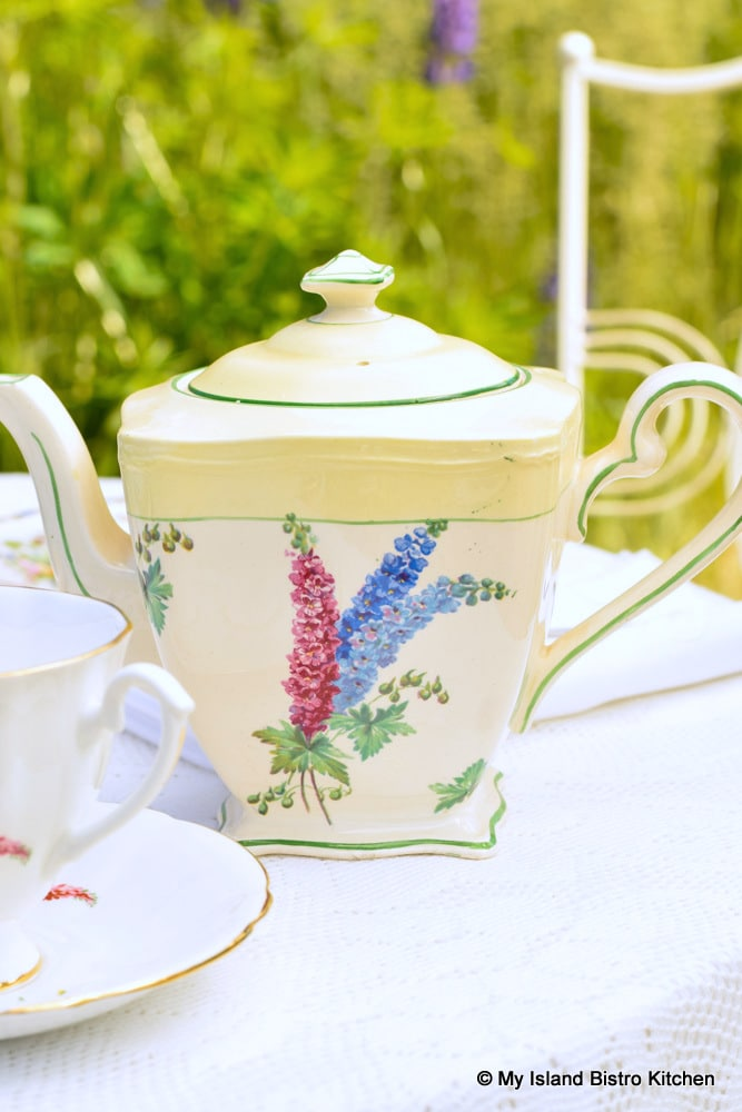 Yellow and white teapot featuring larkspur