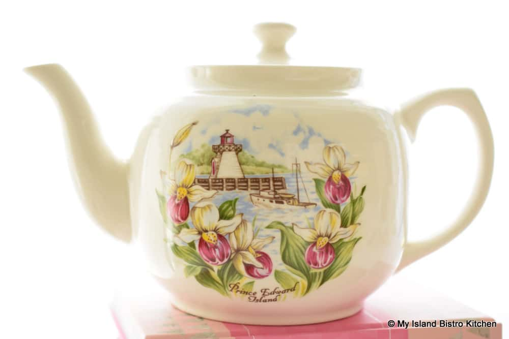 Teapot with flowers, lighthouse, and fishing boat