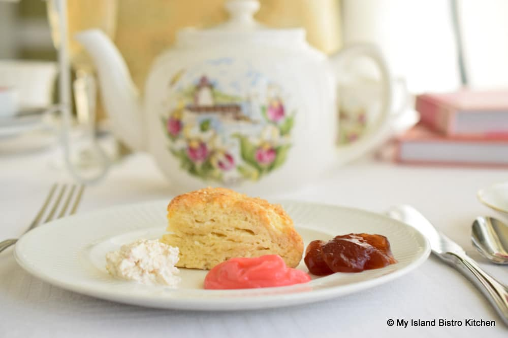 Scones with toppings on plate and pretty teapot in background