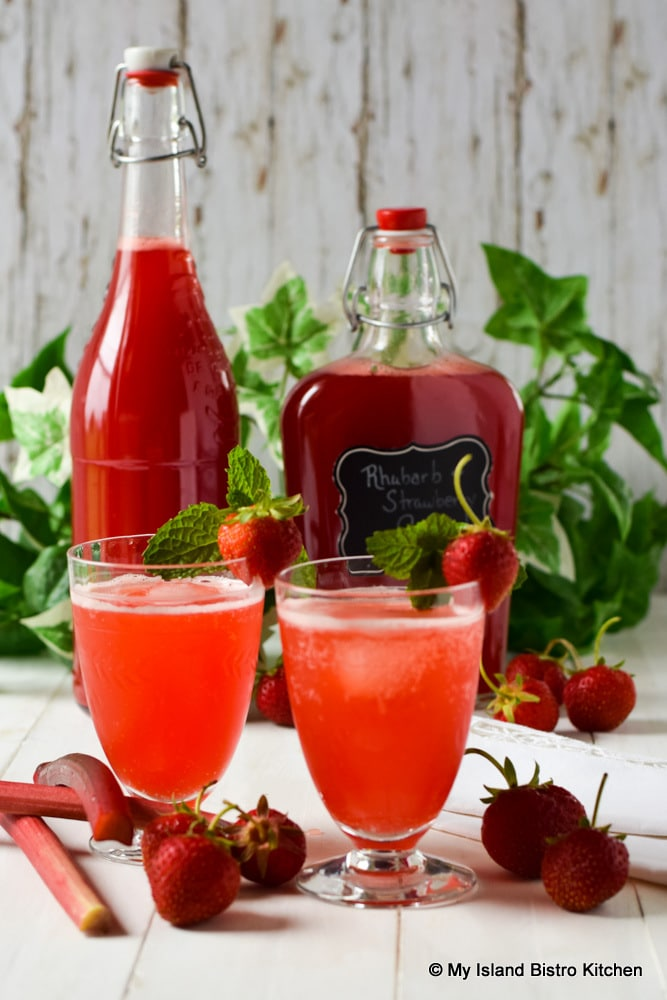 Bottles and glasses filled with Rhubarb and Strawberry Cordial