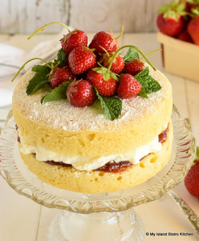 Top view of sponge cake dusted with icing sugar and decorated with fresh strawberries