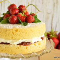Sponge Cake filled with jam and whipped cream and topped with fresh strawberries