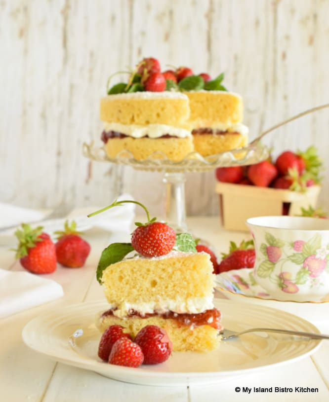 The classic teatime cake - Sponge Cake filled with jam and whipped cream and topped with fresh strawberries