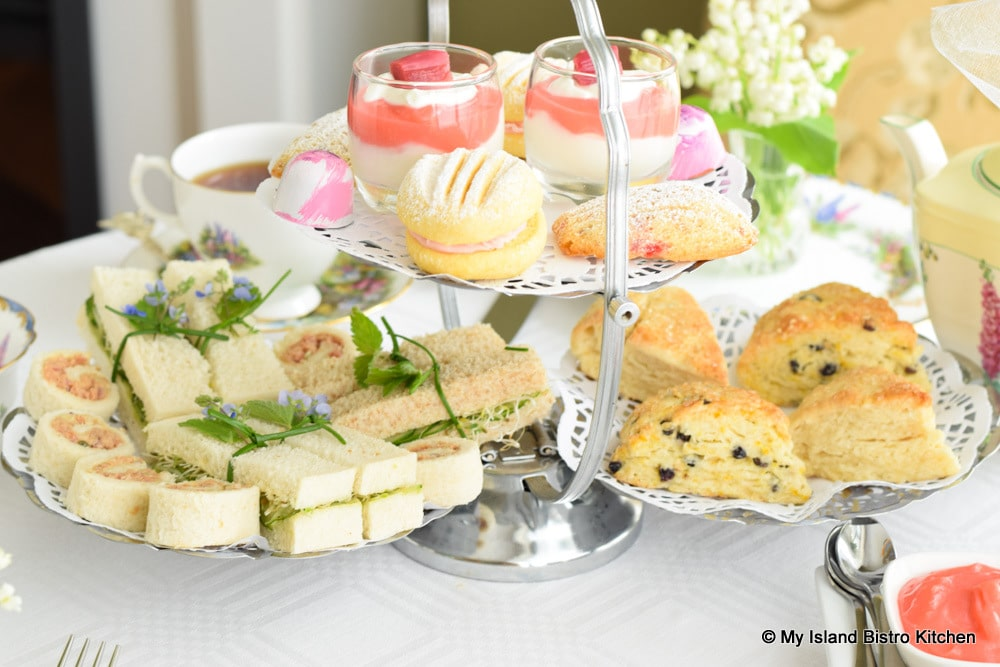 Silver server filled with tea sandwiches, scones, and sweets